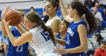 Lehman Lobo Janessa Grogan (15) wrestles away possession of the basketball from a collection of New Braunfels Unicorn players in Tuesday's nondistrict game at the Lobo Den. (photo by Tracy Stirman)