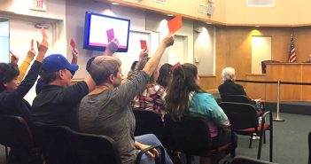 Anti-fluoride protesters held up signs asking to be heard at the Jan. 3 Buda City Council meeting. (photo by Samantha Smith)