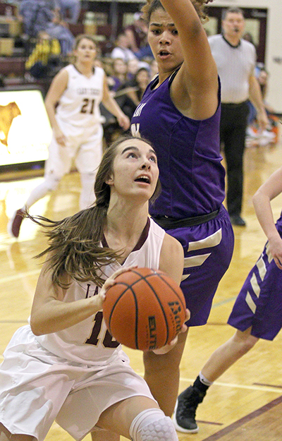 Dripping Springs' senior Nicole Nading looks for a shot under the basket and the outstretched arm of Marble Falls' Meghan Owens. Getting shots off and rebounding was a tall order for the Tigers, who were at a height disadvantage against Marble Falls, but one the Lady Tigers almost overcame. (photo by Wayland D. Clark)
