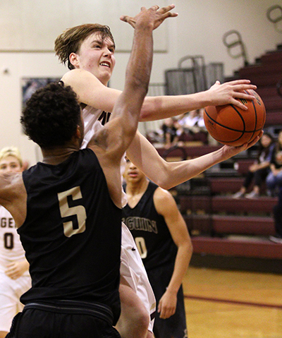 Dripping Springs' Nick Breen makes an awkward shot at the basket for two points as he goes around Seguin's Jaren Sayles (5) defending on the play. Breen finished with 10 points. (photo by Wayland D. Clark, wfotos.com()