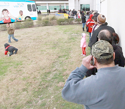 Approximately 100 people patiently wait in line near the entrance of Seton Medical Center Hays for Ascension's Medical Mission at Home to open Saturday morning. People were in line for as long as three hours for the event, which offered free healthcare services for area residents. (photo by Moses Leos III)